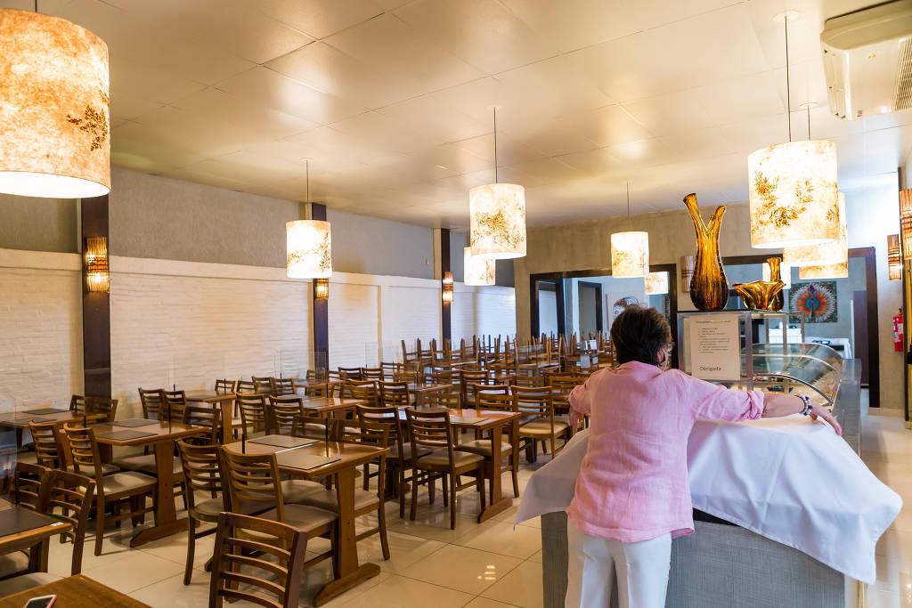 Maria Tereza, dona do restaurante Hibisco, na Vila Olímpia, já colocou divisórias de acrílico e separou as mesas - Ronny Santos/ Folhapress